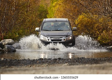 Murmansk region, Russia - September 2018: A pick-up truck to Isuzu d-max is wade across a river, splashes of water are flying against the backdrop of a beautiful autumn forest. Off road tourism