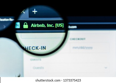 Murmansk, Russian Federation - 18 April 2019:  Airbnb web site homepage. Airbnb inscription visible on screen through magnification magnifier. Dark key