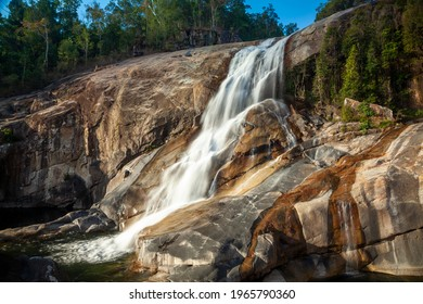 Murray Falls Rock Pool Waterfall Queensland, Australia. Stream of water from top right to bottom left. Cascade of water flowing over rocks inside forest with blue sky.