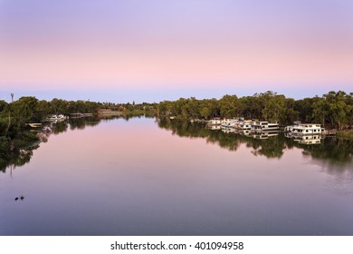 Murray river bend near Mildura with calm and still flow of water at sunrise. Residential and fishing floating houses docked to Victorian and NSW sides of the river.