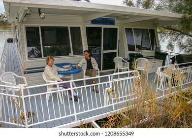 Murray River, South Austraila - Jun 5 2006: A middle age couple enjoy a drink on the front deck of a houseboat. Houseboat holidays are very popular in Australia.