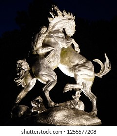MURRELLS INLET, South Carolina/USA; JULY 4, 2018; Dueling Stallions sculpture display by Anna Hyatt Huntington in aluminum at night at entrance of Brookgreen Gardens just outside of Myrtle Beach