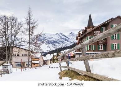 MURREN, SWITZERLAND - DECEMBER 22, 2013: Winter chalets and cabins facing a mountain