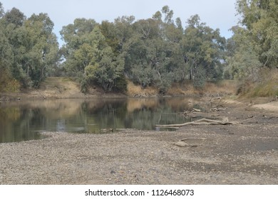 The Murrumbidgee river very low on water with tree reflection on water on a cloudy day