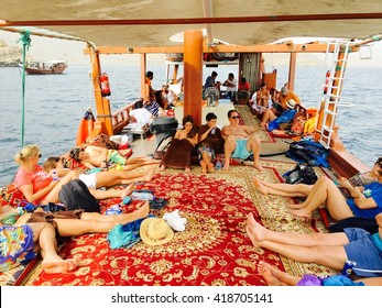 Musandam, Oman - 30th March 2016: Tourists on a Dhow boat, enjoying sun and sailing in Strait of Hormuz, in gulf of Oman, Musandam, Oman