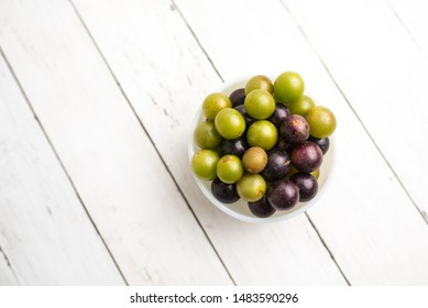 Muscadine grapes are also known as swamp grapes, Florida grapes in a bowl on wood background