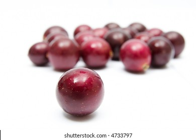 Muscadine grapes on a white background.