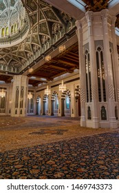 Muscat / Oman - 03.19.2019; Interior of Sultan Qaboos Grand Mosque in Muscat, Oman. The main prayer room with beautiful hand-woven rug, richly decorated columns and vault.