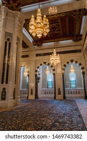 Muscat / Oman - 03.19.2019; Interior of Sultan Qaboos Grand Mosque in Muscat, Oman. Passage with decorated golden lamps, black and white arches.