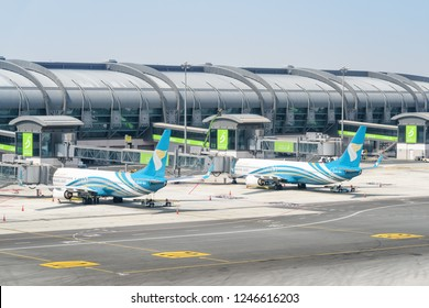 Muscat, Oman - 17 October, 2018: Oman Air aircraft parked on the apron of Muscat International Airport. The airport is the main base of the national airline. View of gates at departure area.