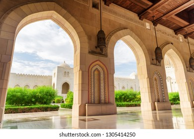 Muscat, Oman - 17 October, 2018: Beautiful view of the Sultan Qaboos Grand Mosque from arched passageway. Islamic architecture. The Muslim place is a popular tourist attraction of the Middle East.