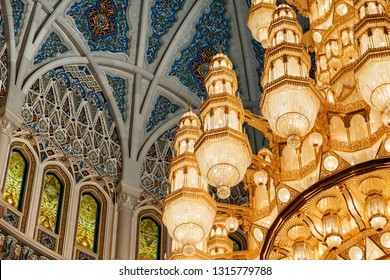 Muscat, Oman - 17 October, 2018: Wonderful view of ceiling and chandelier above the main prayer hall of the Sultan Qaboos Grand Mosque. Beautiful details of amazing interior of the Muslim place.