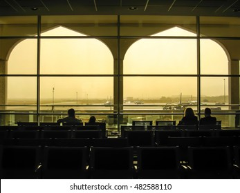 Muscat, Oman - April 16, 2013: Couple passengers seated watching the aircrafts during waiting for boarding by the morning sunlight shines into the international airport terminal of Muscat in Oman.