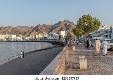 MUSCAT, OMAN - AUGUST 29, 2014: People walking along the Muttrah Corniche in the afternoon, with Muscat's craggy mountains in the background