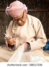 Muscat, Oman - Feb 4, 2017: An Omani man weaving a traditional fishing net by hand.
