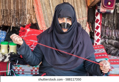 Muscat, Oman - Feb 4, 2017: An old Omani woman dressed in a traditional clothing showing off her wares on a market.