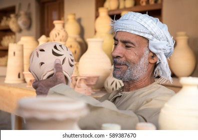 Muscat, Oman - Feb 4, 2017: An old Omani man in a traditional dress showing off his pottery.