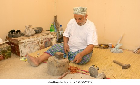 MUSCAT, OMAN - FEBRUARY 1, 2008: A bearded Omani coppersmith, wearing a traditional kuma (cap), at work in Muscat, in the Sultanate of Oman.