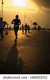 Muscat, Oman - January 19 2018: A group of runners running along the beach road during the Muscat Marathon with the morning sun raising in the background.