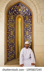 Muscat, Oman - May 12, 2019: Local man in traditional arabian clothes sitting in Sultan Qaboos Grand Mosque