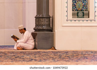 MUSCAT, OMAN - NOVEMBER 30, 2017: a man prays in Sultan Qaboos Grand Mosque in Muscat, Oman