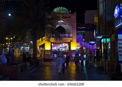 MUSCAT, OMAN - OCTOBER 24 2013: Muscat at Night. Night view of Oman capital at night, in its center, facing the Mutrah souq, trough restaurants and people.