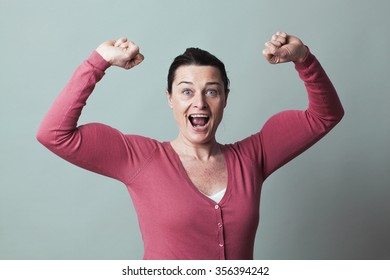 muscle concept - laughing beautiful 40s woman proud of flexing her big muscles for metaphor of success and female power,studio shot, low contrast effect