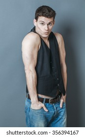 muscle concept - shy young man putting his big muscular arms in his jeans pockets embarrassed to show his strength,studio shot,low contrast effect