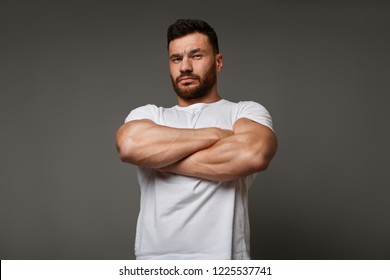 Muscle concept - suspicious young man with crossed big muscular arms showing his arrogant strength and male power, looking down at camera