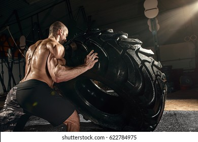 muscle cross strongman training - man flipping big tire