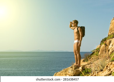 Muscle guy on the rocks looking at the sea - young man watch something in distance with bag - amazing blue ocean view wild holidays and travel concept