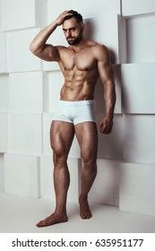 Muscle male model in white underwear posing on grafic white background. Studio shoot.