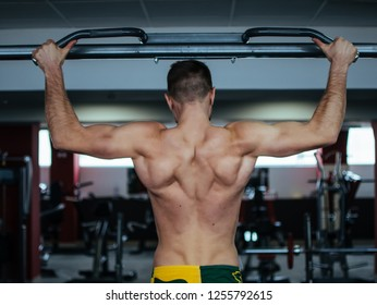 Muscle man making pull-up on horizontal bar in the gym