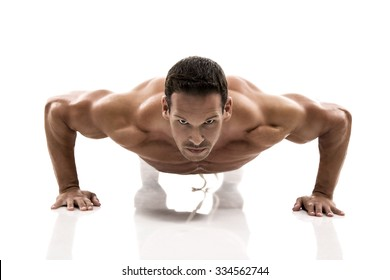 Muscle man making pushups in studio, isolated over a white background