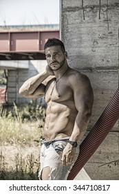 Muscle man shirtless outdoors in building site. Construction worker