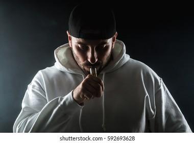 Muscle man vaping an electronic cigarette.On black Backgrpund
