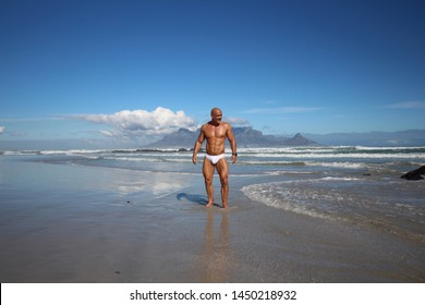 muscle man in white speedo at sea with Table Mountain background
