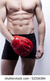Muscle man's body in gym, with boxing glove