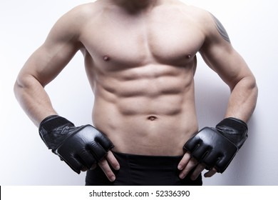 Muscle man's body in gym, with boxing gloves