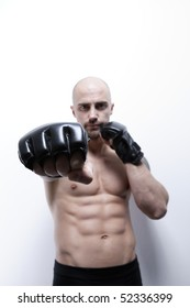 Muscle man's body in gym, with boxing glove, showing abs, six packs