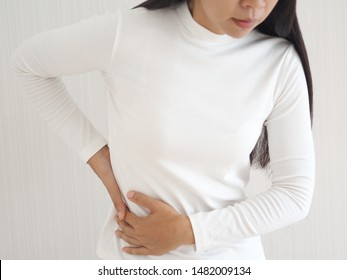muscle pain in asian woman and she use hand touching and press her flank waist symptom of swelling cause of lift heavy use for health care concept.