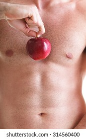 Muscle sexy naked young man torso and red apple in hands diet