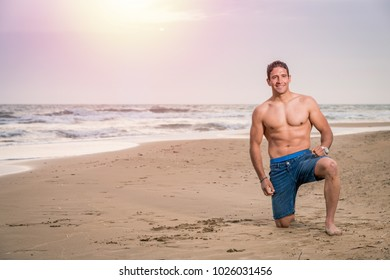Muscle sexy wet naked young man posing on the beach
