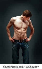 Muscle sexy young man over dark background