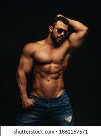 Muscle shirtless man in sunglasses at black backgorund