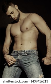 Muscle strong beautiful stripped male model in denim blue jeans on black isolated font background