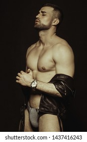 Muscle strong beautiful stripped male model in black leather jacket and underwear on black isolated font background