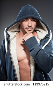 Muscled fitness man. Cool looking. Tough guy. Brown eyes. Bald. Wearing blue hood shirt. Tanned skin. Studio shot isolated on grey background.