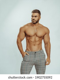 Muscled handsome man in classic pants. Big shirtless hunk wearing checkered trousers.