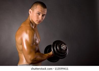 Muscled male bodybuilderweight, dumbbell, raise, swing